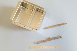 Sample parts, one with value-added riveting